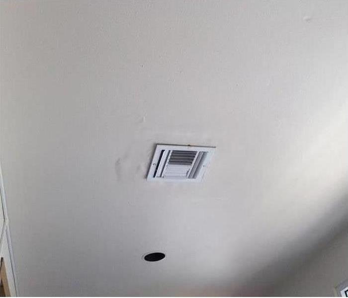 picture of a ceiling vent that has bubbling paint around it from water damage