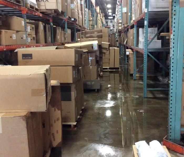 Warehouse with shelves full of boxes and water on the cement floor below